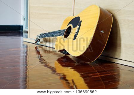 Electric Guitar lying on wooden cabinet in bedroom
