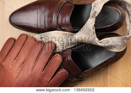 Classic mens brown shoes tie gloves on wooden floor can be used as background