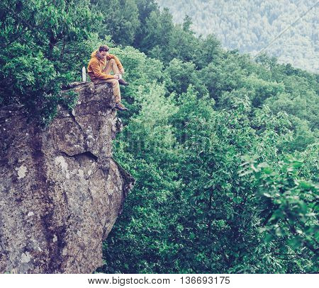 Traveler sitting on top of cliff over the summer forest and pouring tea from thermos to cup.