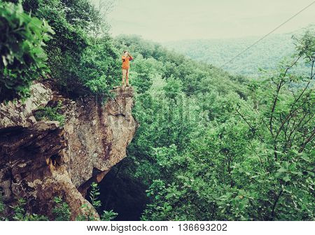 Traveler standing on edge of cliff and looking in binoculars into the distance in summer outdoor