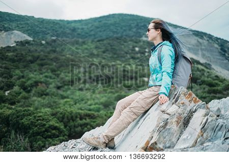 Beautiful traveler young woman sitting on peak of cliff and enjoying view of mountains in summer outdoor