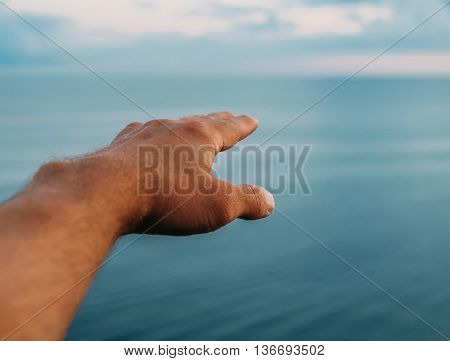 Male hand pointing into the sea distance point of view