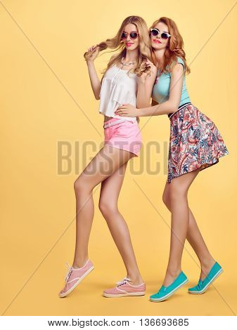 Fashion. Fashion hipster woman, fashion summer outfit having fun. Fashion sisters friends crazy cheeky emotions.Girl in fashion sunglasses, fashion wavy hairstyle posing on yellow.Unusual creative fun