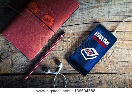 Learning english. Top view of mobile, pencil, notebook and earphones, with english dictionary application on mobile screen.