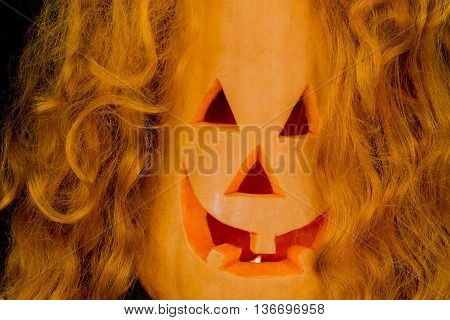 Halloween pumpkins with very scary face and with red hair, burning candle on black background close-up