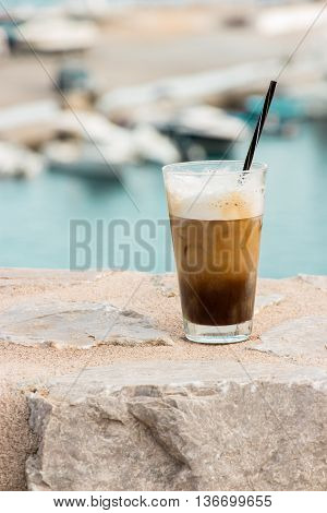 Right cup of coffee with ice cream lest seascape on the background of the sea port. Coffe with ice and cream. Vertical. Daylight.