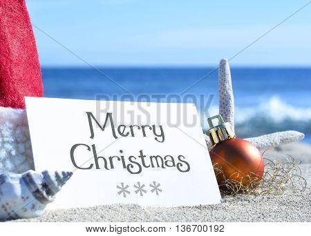 Merry christmas card with christmas decoration and sea shell on a tropical beach. Christmas holidays. Greeting card on the beach.