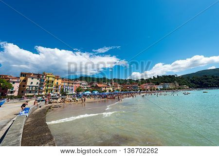 SAN TERENZO LERICI ITALY - JULY 10 2014: San Terenzo (St. Terenzo) beach crowded with bathers on a sunny day in july. The beach is located in the small village of San Terenzo tourist resort in Lerici in the Gulf of La Spezia Liguria Italy
