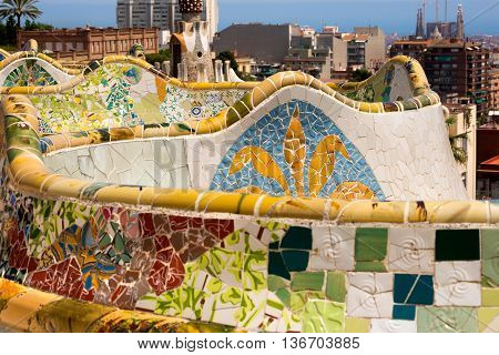 BARCELONA SPAIN - JUN 10 2014: Ceramic bench and building in the Park Guell designed by the famous architect Antoni Gaudi (1852-1926). UNESCO World Heritage Site