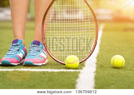 Close up of female feet with sneakers. Athlete is standing on tennis court near balls and racket