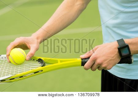 Close up of male hands putting tennis ball on racket. Man is standing on tennis court. Tracker on his arm