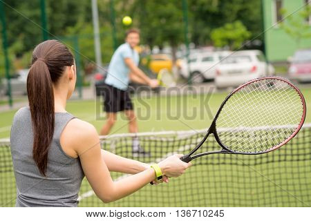 Cheerful woman and man are playing tennis on court. They are standing opposite the net and holding rackets. Focus on female back