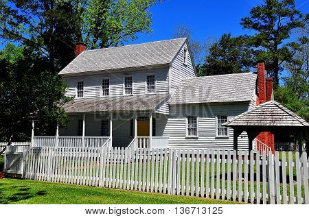Bath North Carolina - April 25 2016: Circa 1820 wooden frame Bonner House with portico ell addition and white fence *