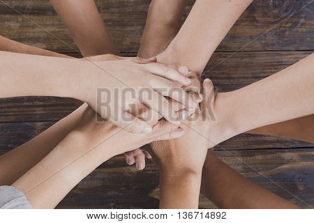 People Put Hand Together For Use As Unity Teamwork Concept