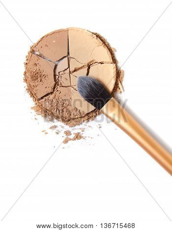 Smashed bronze face powder with make up brush isolated on a white background