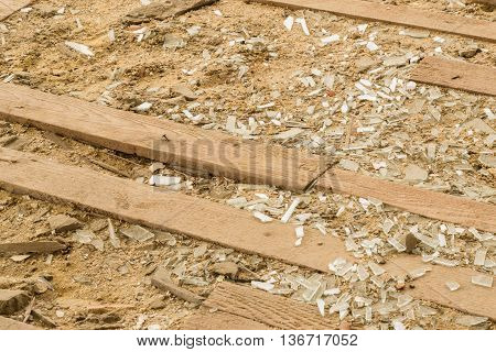 Broken Glasses on Sandy Floor with Planks