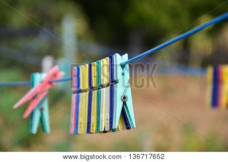 Empty colorful clothes pegs on string in garden