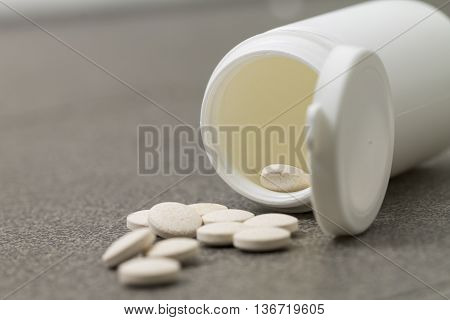 Vitamin pills drugs acid is scattered out of the jar on a black background. Drugs are jumping out of the white jar.