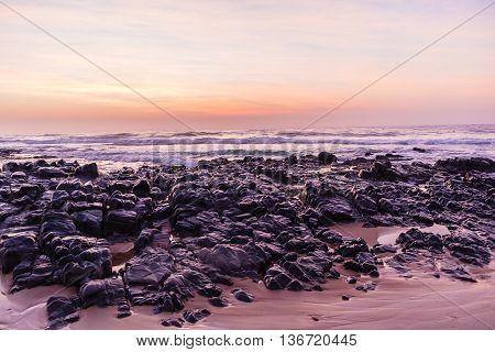 Beach rocky shoreline ocean waves  dawn morning landscape.