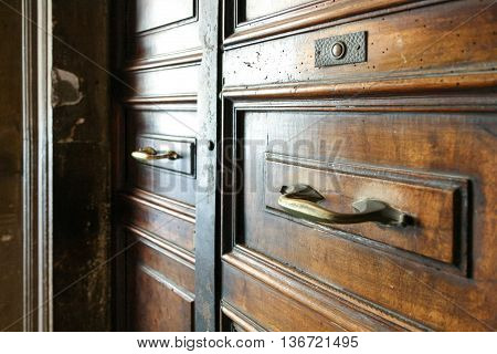 Old wooden double-wing framed doors with brass handles and button doorbell.