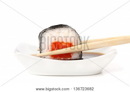 Sushi rolls with salmon rice and nori in chopsticks dipped in soy sauce isolated