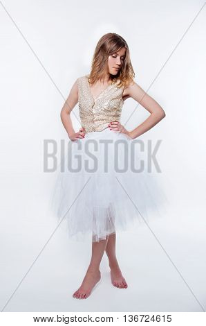 Glamorous beautiful blonde woman in golden sequin outfit and tulle white skirt with glitter makeup