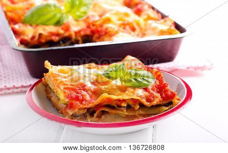 Aubergine and zucchini lasagna slice on plate