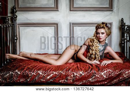 Blonge Woman in medieval corset  historic dress and lingerie  posing in bed