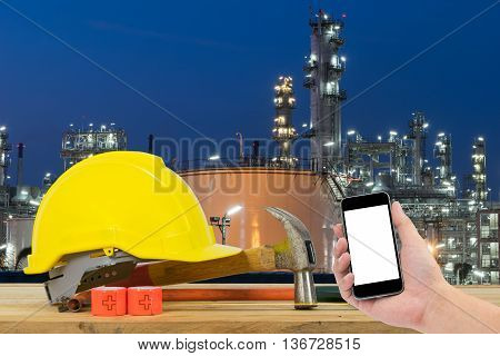 Front view of Hand holding the black smartphone and Yellow Safety Helmet Hammer Cutting tools on front of Oil refinery industry in night