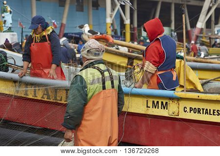 VALPARAISO, CHILE - JULY 1, 2016: Fishermen cleaning and tidying fishing nets in the fishing harbour in Valparaiso, Chile.