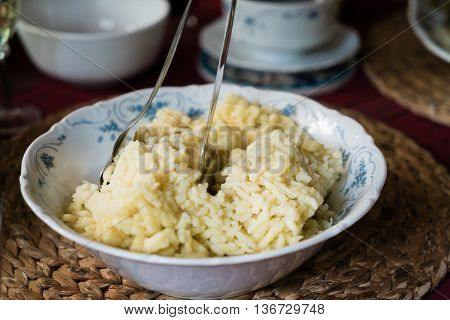 Traditional German Spaetzle, egg noodles made by pouring batter through a colander into boiling water, served in a rustic frying pan with blue and white checked cloth on a dark background