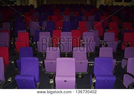Empty auditorium in penumbra with multi colored seats