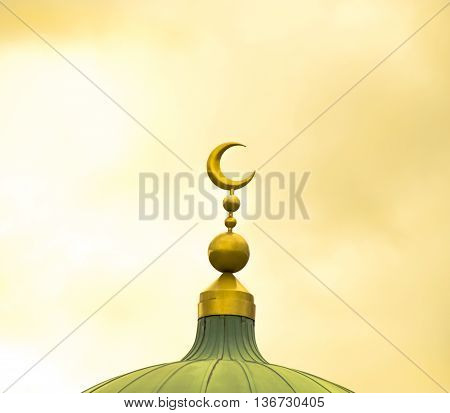 Islamic symbol on mosque's cupola on yellow cloudy background
