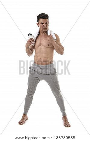 40s attractive sport man and bodybuilder with naked torso showing fit and muscular body posing angry cool attitude holding water bottle and neck towel in mature bodybuilding concept
