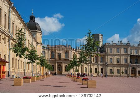 Gatchina, Russia - June 2, 2016: Gatchina Palace. Palace Square and the main entrance. Central building with balconies, lateral tower. Tourists at the entrance to the museum.