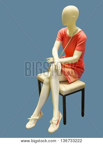 Sitting female mannequin wearing pink summer dress against blue background. No brand names or copyright objects.