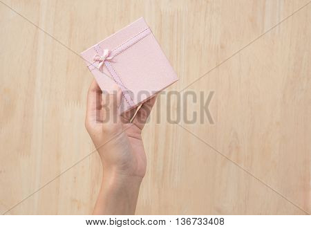 hand holding colourful vintage gift box on wooden table top view background with copy space for idea simple text.