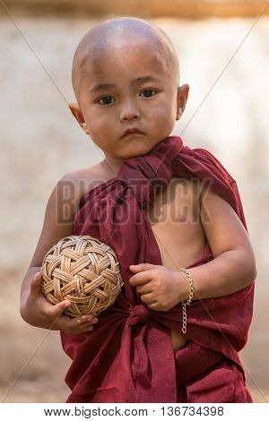 BAGAN MYANMAR - JANUARY 20 2016: Unidentified young kid monk standing and looking at Bagan pagoda