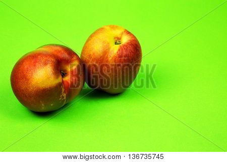 Two fresh nectarines on a light green cardboard slightly grainy background. Close horizontal view.