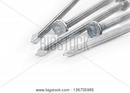 Close up of steel concrete nails on white background with cast shadow and light reflection