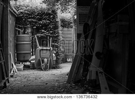 Two metal garden wheelbarrows on the bare ground and rainwater tank near barn