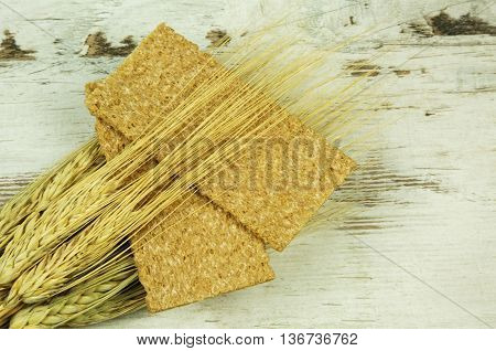 Two crisp bread and ears of corn on wooden background i vintage style. Flat horizontal view.