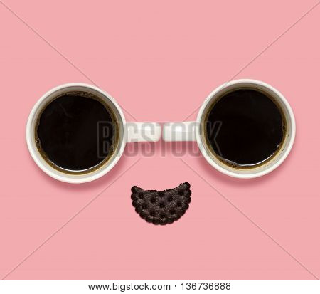 Creative concept photo of coffee cups with a cracker in the shape of a smiling face on pink background.