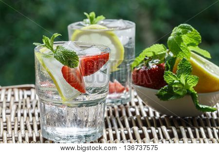 Mineral water with lemon strawberries and mint. Summer refreshment drink. Detox. Selective focus
