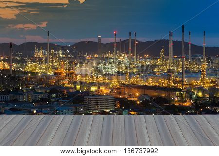 Opening wooden floor, Aerial view, Oil refinery lights at twilight,mountain background