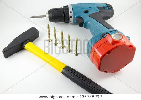 Cordless screwdriver screws and a hammer on a white background