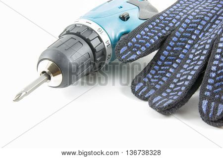 Cordless screwdriver and gloves on a white background