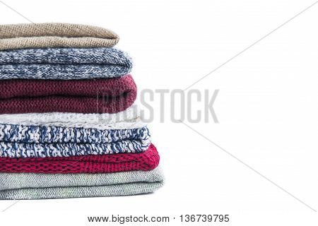 Pile of knitted winter colored clothes on wooden background, sweaters, knitwear, space for text