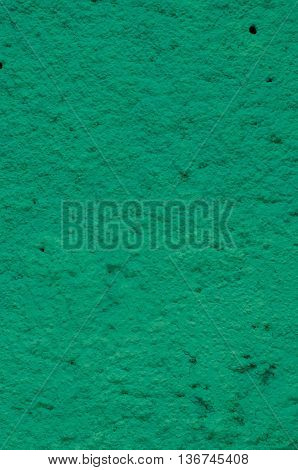 Background of a green stucco coated and painted exterior rough cast of cement and concrete wall texture decorative coating