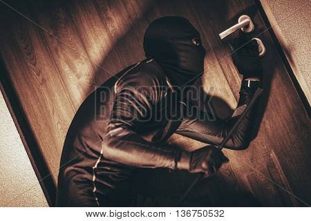 House Security Concept with Home Burglar in Action Trying To Break Into the House.